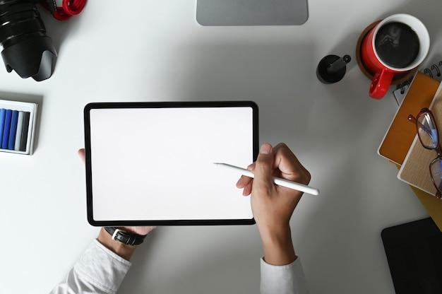 La vista dall'alto di un giovane designer grafico utilizza la scrittura con penna stilo sul tablet