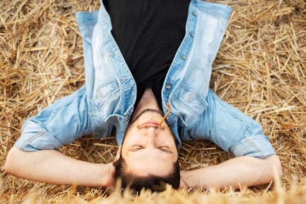 Vista dall'alto di un giovane ragazzo con un picco di grano in bocca che giace sulla terraferma.