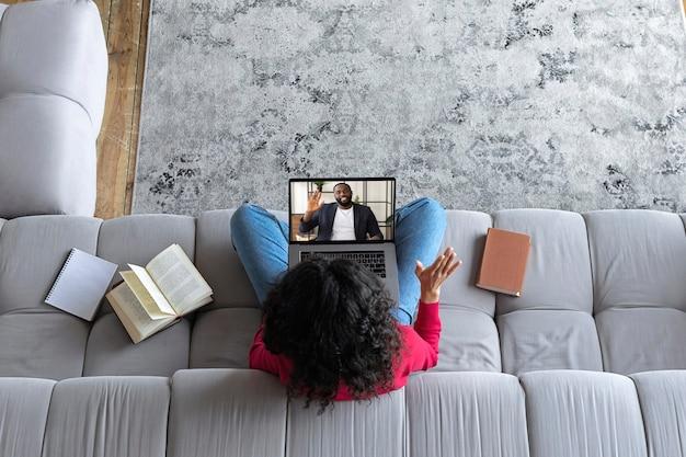La giovane donna vista dall'alto ha una conferenza online o una videochiamata mentre è seduta sul divano a casa con un insegnante o un amico. istruzione online o concetto di lavoro a distanza