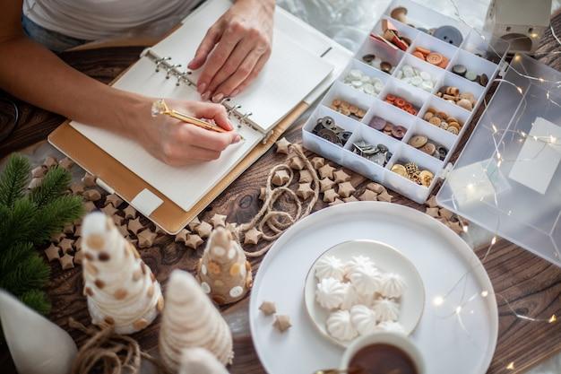 La vista dall'alto della giovane donna sta scrivendo gli obiettivi per il nuovo anno 2021 sul diario sulla scrivania con decorazioni artigianali per l'albero di natale, stelle, bottoni e tè con marshmallow. concetto di pianificazione di nuovi obiettivi.