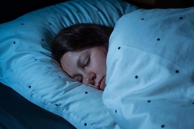 Vista dall'alto della giovane donna che dorme comodamente su un letto di notte, i colori notturni blu