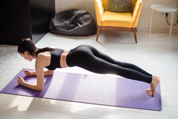 Vista dall'alto della giovane donna in abbigliamento sportivo che fa esercizi di plancia per allenare gli addominali sul tappetino da yoga. concetto di stile di vita attivo e sano.