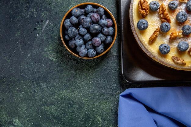 Torta di miele squisita vista dall'alto con mirtilli e noci all'interno della superficie scura del piatto
