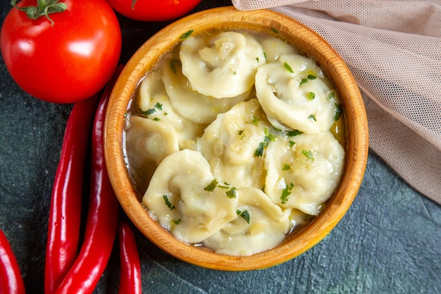 Vista dall'alto gustosi gnocchi di carne all'interno del piatto di legno con pomodori freschi sulla superficie scura