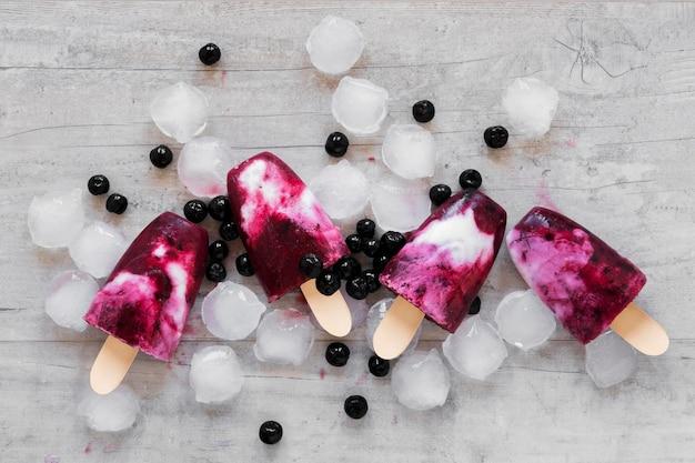 Vista dall'alto di gustosissimi ghiaccioli con ghiaccio e mirtilli