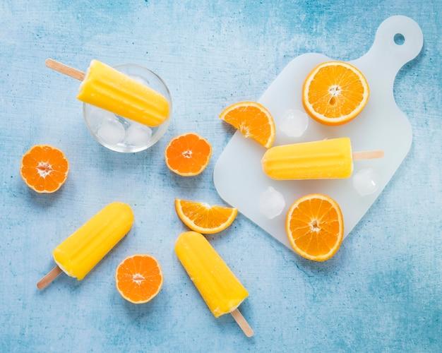 Vista dall'alto di gustosissimi ghiaccioli con arancia e ghiaccio