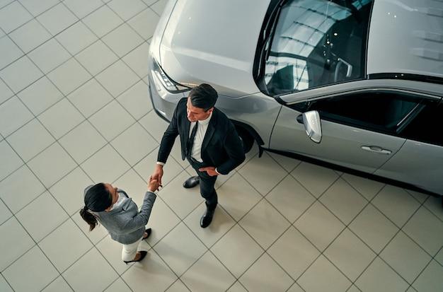 Top viewc ar rivenditore e cliente di concessionaria auto che agitano le mani. manager e cliente che fanno affari sull'acquisto del veicolo. moderno showroom di auto.