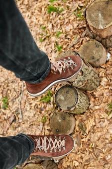 Top viewwoman in piedi con scarponi da montagna su foglie autunnali e fondo in legno
