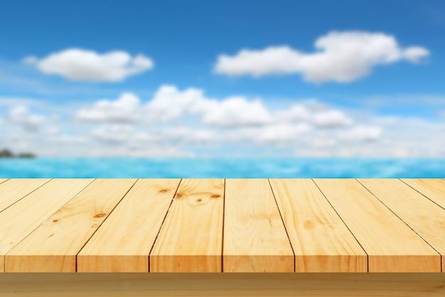 Piano del tavolo in legno con mare sfocato e cielo blu
