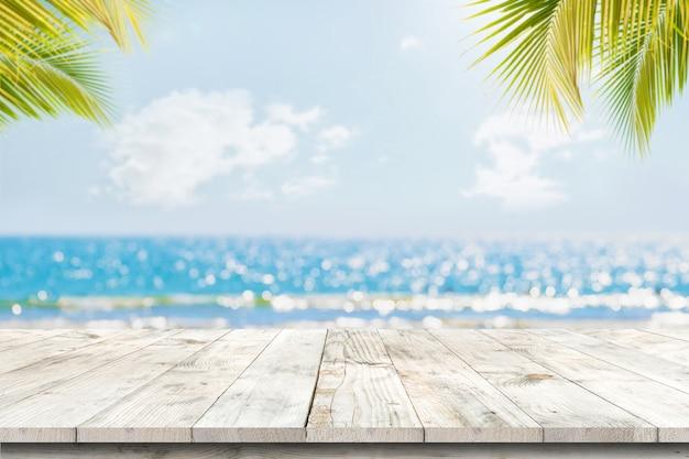 Parte superiore della tabella di legno con vista sul mare e foglie di palma, luce del bokeh della sfuocatura del mare calmo e cielo alla spiaggia tropicale