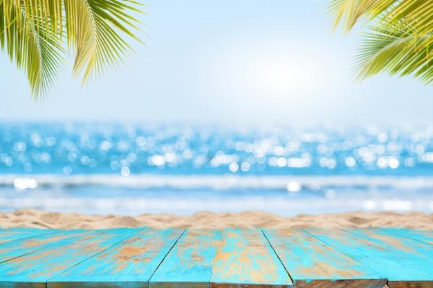 Parte superiore del tavolo in legno con vista sul mare e foglie di palma