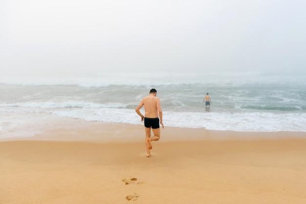 Uomo topless che corre dalla spiaggia nell'oceano tempestoso nebbioso.