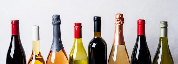 Top di diversi tipi nuove bottiglie di champagne, vino bianco, rosso su sfondo chiaro