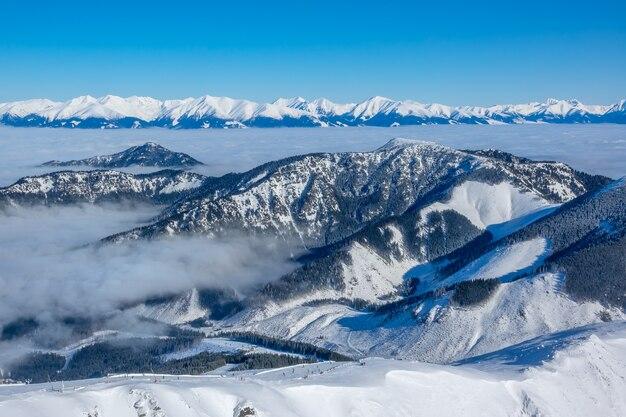 Le cime delle montagne invernali e la nebbia nelle valli in una stazione sciistica. tempo soleggiato e cielo blu. vista aerea