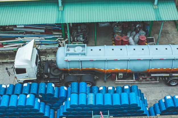 Vista dall'alto trasporto camion fusti chimici barili di petrolio fusti chimici blu impilati orizzontalmente