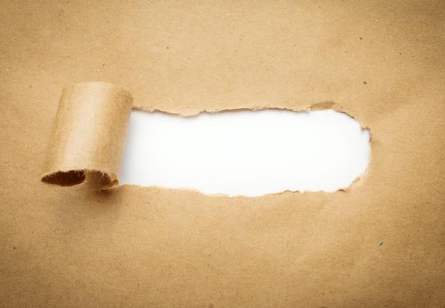 Carta marrone strappata con spazio bianco vuoto.