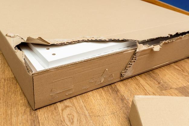 Scatola di cartone strappata e danneggiata, imballaggio di mobili per il montaggio