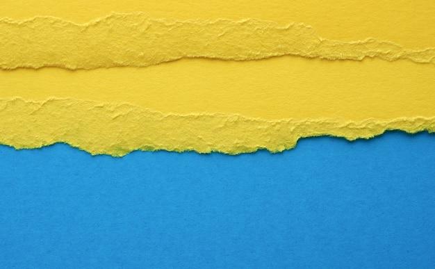 Bordi strappati di carta gialla su sfondo blu