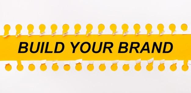 Striscia di carta strappata su sfondo giallo con testo costruisci il tuo marchio