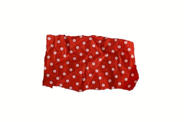 Pezzo strappato di carta rossa con pois bianchi isolati su sfondo bianco.