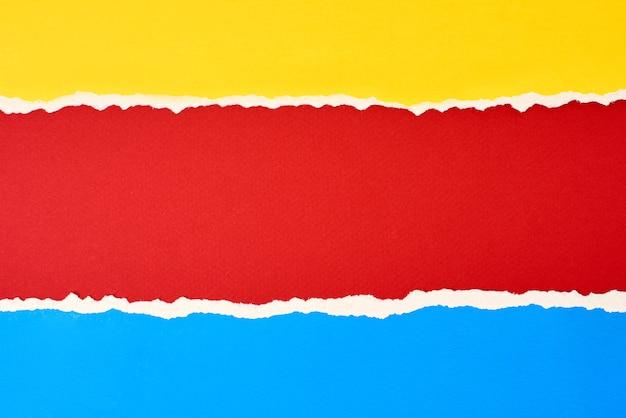 Bordo di carta strappato strappato con uno spazio di copia, sfondo di colore rosso, blu e giallo