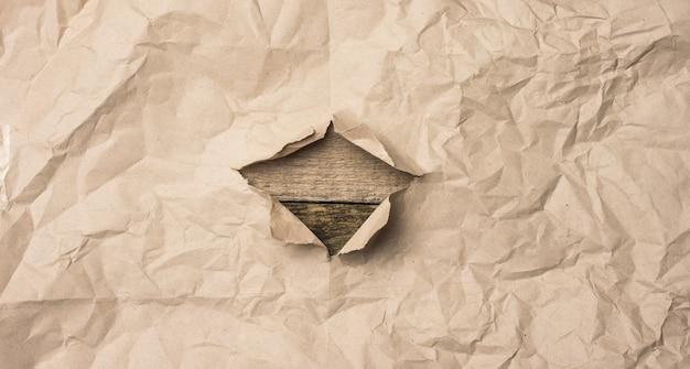 Foglio strappato di carta marrone con un foro su uno sfondo di legno da vecchie tavole