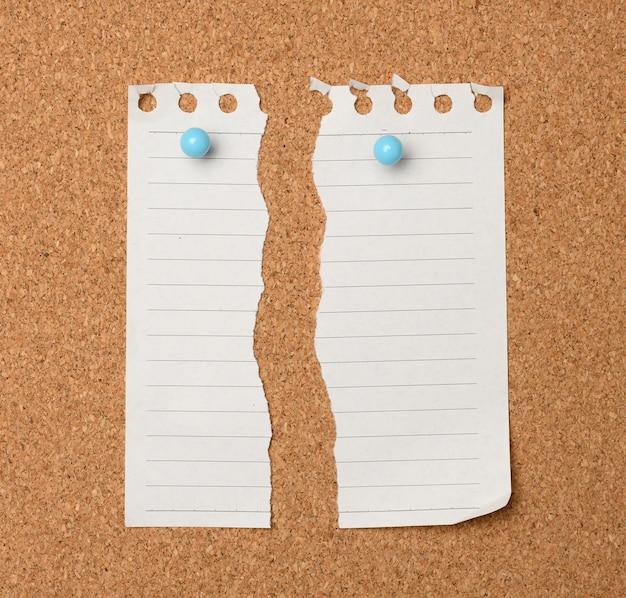 Foglio di carta bianco strappato in una linea appesa a una bacheca di sughero marrone, da vicino