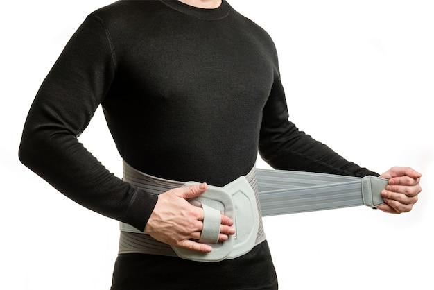 Torso di un uomo in un corsetto ortopedico su uno sfondo bianco.