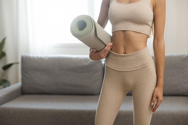 Torso di giovane donna che tiene nelle mani materassino yoga o fitness dopo aver lavorato a casa nel soggiorno