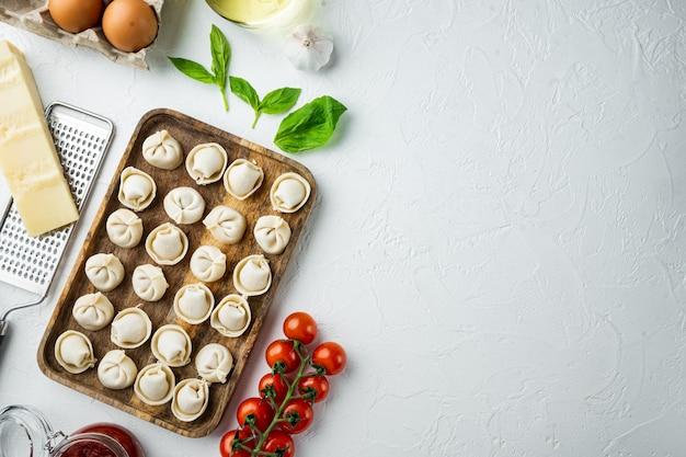 Gli ingredienti dei tortellini hanno messo nel vassoio di legno sulla disposizione piana di vista superiore bianca