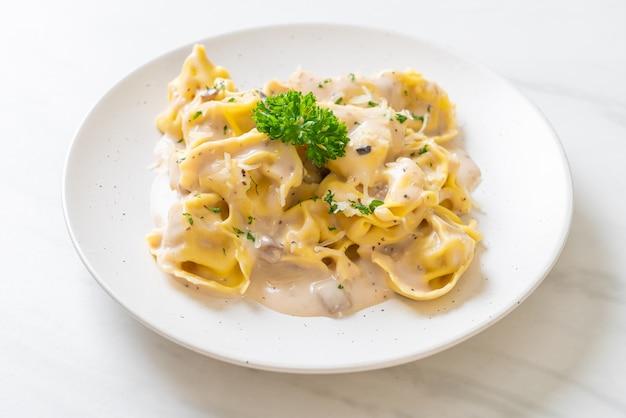 Tortellini con salsa di crema di funghi e formaggio. stile di cibo italiano