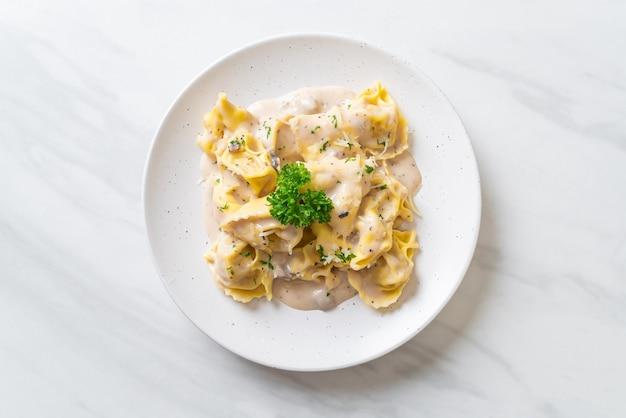 Tortellini con salsa di crema di funghi e formaggio - stile alimentare italiano