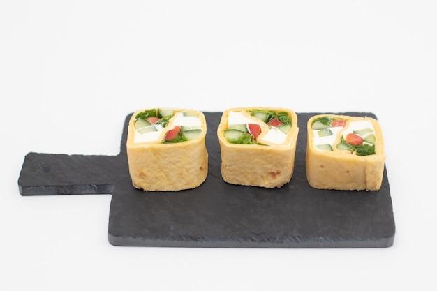 Rotoli di tortilla con verdure servite su una tavola di ardesia nera.