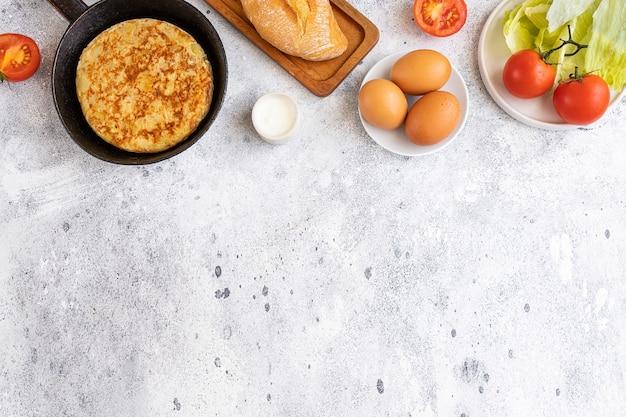 Tortilla frittata spagnola fatta con uova e patate in padella servita con insalata tradizionale, maionese e pane.