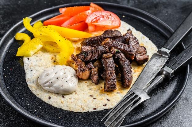 Tortilla con bistecca di carne di manzo e insalata fresca su un piatto rustico