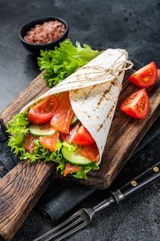 Tortilla avvolgere il rotolo di salmone con insalata, verdure. sfondo nero. vista dall'alto.