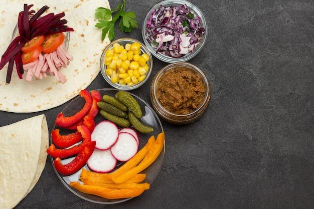 Impacchi di tortilla e ripieno di verdure per tortilla in ciotole di vetro.
