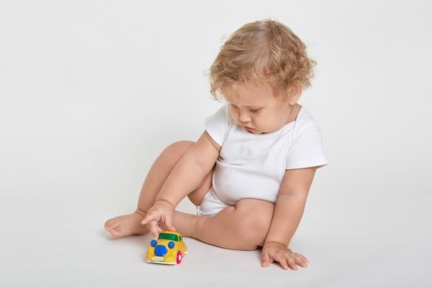 Tot con capelli ondulati biondi che gioca con la macchinina mentre è seduto a piedi nudi sul pavimento
