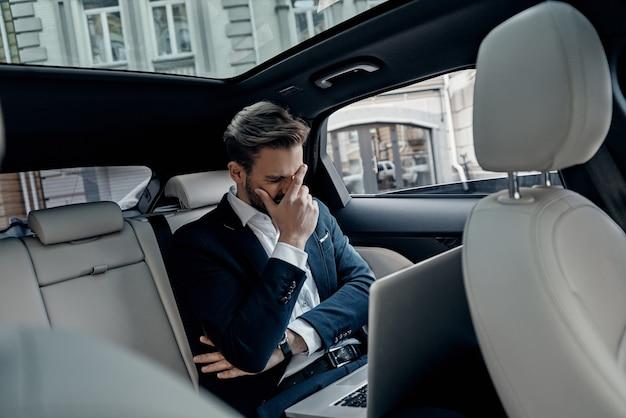 Disastro totale! giovane frustrato in tuta intera che lavora usando il laptop e copre il viso con la mano mentre è seduto in macchina