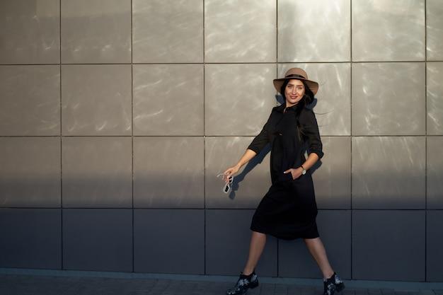 Total look per ogni giorno. giovane ragazza attraente attiva attiva del brunette che porta vestito nero alla moda e cappello alla moda. modella in abito giovanile alla moda che cammina sul muro di fondo urbano.
