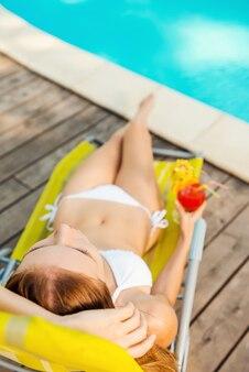 Relax totale a bordo piscina. vista dall'alto di una bellissima giovane donna in bikini bianco che tiene in mano un cocktail mentre si rilassa sulla sedia a sdraio vicino alla piscina