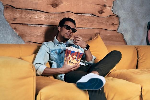 Totalmente spensierato. giovane rilassato in abbigliamento casual che mangia popcorn mentre guarda un film a casa