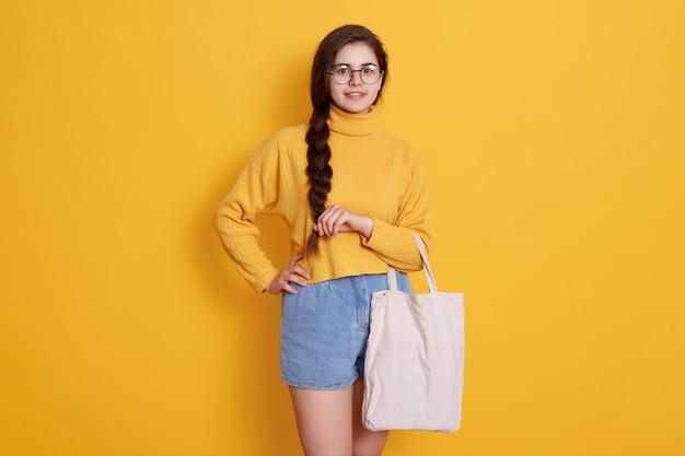 Tote bag nelle mani di una ragazza adolescente carina con codino e occhiali, indossa un maglione e jeans corti, posa isolata sopra il muro giallo