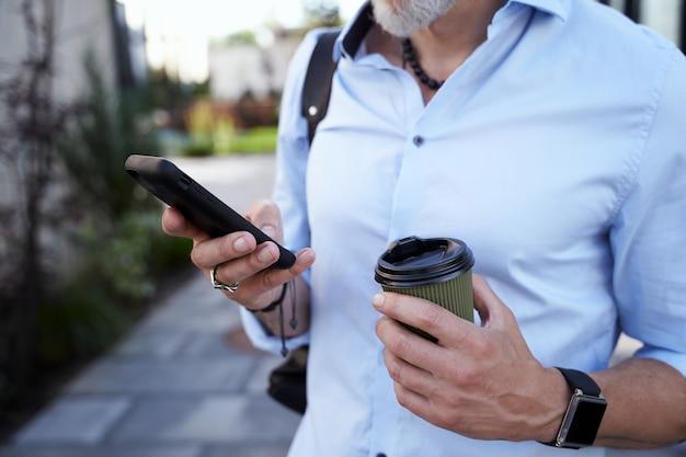 In contatto ravvicinata con le mani di un moderno uomo d'affari di mezza età che usa il suo smartphone mentre