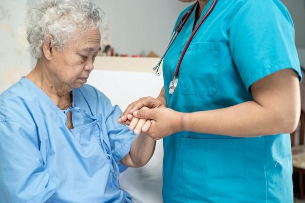 Toccando una paziente asiatica anziana con amore e cura aiutando a incoraggiare ed empatia