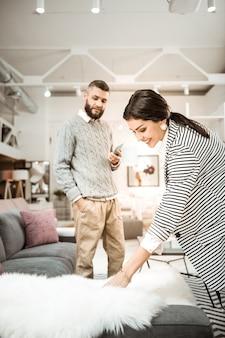 Toccando soffice pelliccia. sorridente signora positiva che mostra soffice decorazione a suo marito mentre lui in piedi con lo smartphone