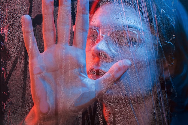 Toccando il bicchiere con la mano. studio girato in studio scuro con luce al neon. ritratto di uomo serio dietro il vetro bagnato