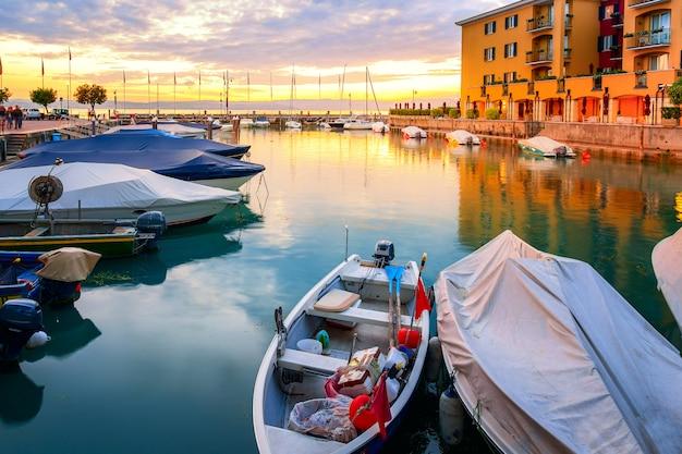 Fai un giro sul molo della barca dalla storica fortezza del castello scaligero nella città di sirmione durante il tramonto