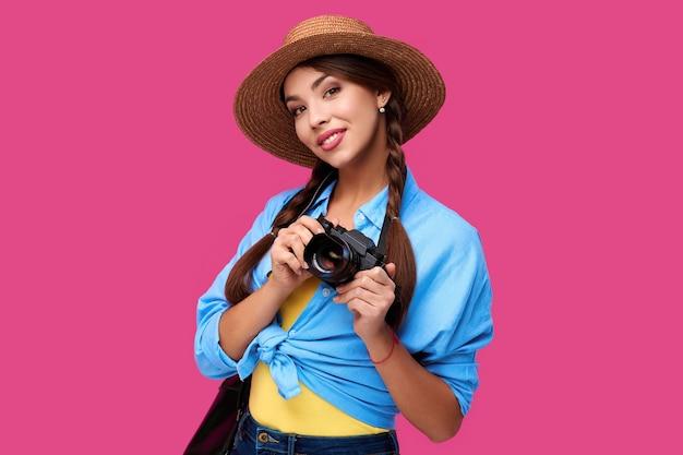 Concetto di turismo. turista felice della donna caucasica in abbigliamento casual estivo che tiene la macchina fotografica della foto, isolata su fondo rosa con lo spazio della copia