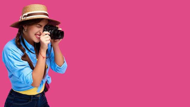 Concetto di turismo. turista sorridente felice della donna in abbigliamento casual di estate che tiene la macchina fotografica della foto e che prende le immagini, isolato su fondo rosa con lo spazio della copia